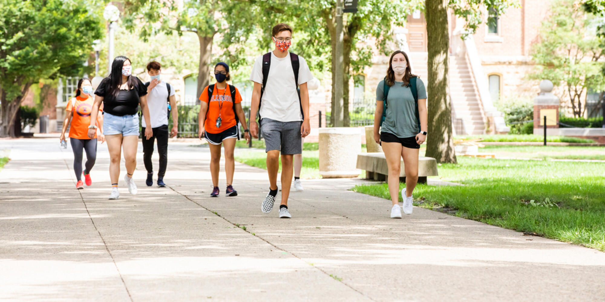 Students walking on campus wearing masks and social distancing