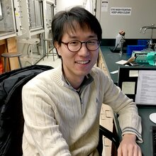 Portrait of research scientist Hong-Jun Cho sitting at a desk in a lab