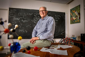 Chemistry professor Thomas Rauchfuss sitting in a classroom in front of a chalkboard with equations written on it.