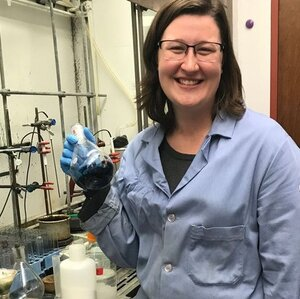 Photo of Amanda East in a blue lab coat in the lab holding a beaker with liquid