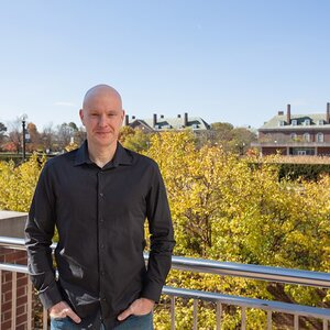Photo of Douglas Mitchell on an outdoor balcony overlooking campus