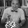 E.J. Corey pictured at his desk holding molecule model